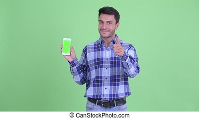 Happy young Hispanic man showing phone and giving thumbs up