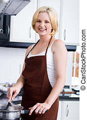 happy young homemaker in kitchen