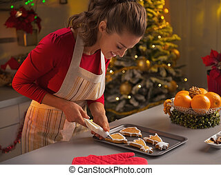Happy young housewife decorating christmas cookies with ...