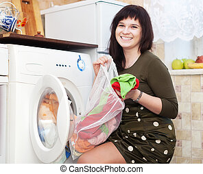 Happy young housewife doing laundry