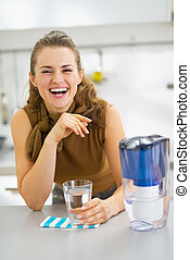 Happy young housewife drinking water from water filter...