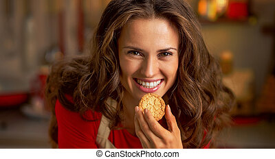 Happy young housewife eating christmas cookie in kitchen