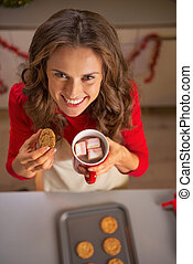 Happy young housewife eating homemade christmas cookies with cup