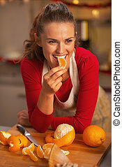 Happy young housewife eating orange in christmas decorated kitchen