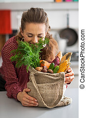 Happy young housewife enjoying freshness of vegetables from loca