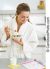 Happy young housewife in bathrobe having healthy breakfast...