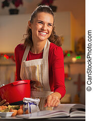 Happy young housewife preparing christmas dinner in kitchen