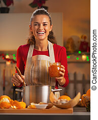Happy young housewife preparing orange jam in christmas decorated kitchen
