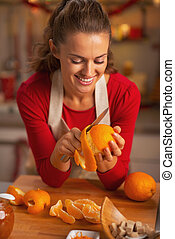 Happy young housewife removing orange peel