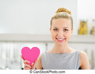 Happy young housewife showing decorative heart in kitchen