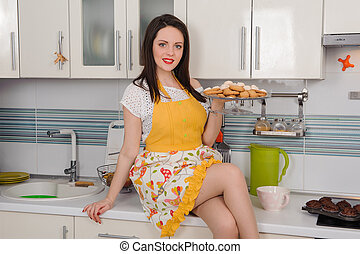 Happy young housewife with cookies in kitchen