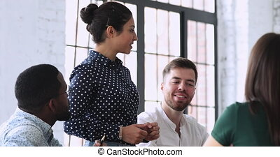 Happy young indian businesswoman standing at table, sharing project ideas with focused mixed race investors at briefing meeting. Professional hindu female mentor coaching millennial colleagues.