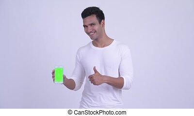 Happy young Indian man showing phone and giving thumbs up