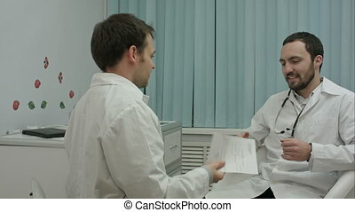Happy young intern shows to mentor doctor results of their medical research work