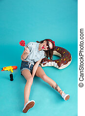 Happy young lady sitting and eating candy. - Photo of happy...