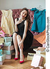 Happy young lady sitting on sofa indoors choosing shoes