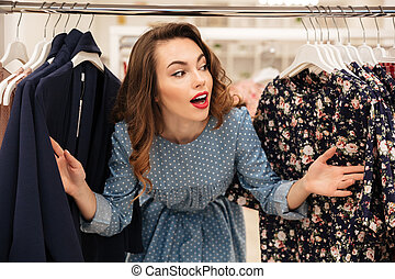 Happy young lady standing in clothes shop - Image of happy...
