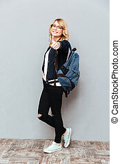 Happy young lady student wearing glasses with backpack