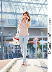 happy young lady walking and talking on mobile phone