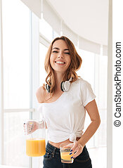 Happy young lady with headphones drinking juice - Picture of...
