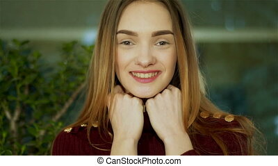 happy young lady with nice make up looking at the camera at home