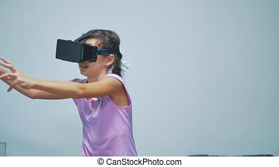 Happy young little girl using 3d goggles a virtual reality...