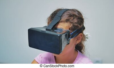 Happy young little girl using 3d goggles a virtual reality ...