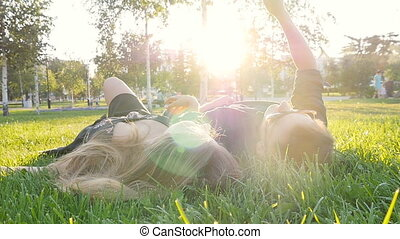Happy young loving couple making selfie with smart phone while lying on the grass