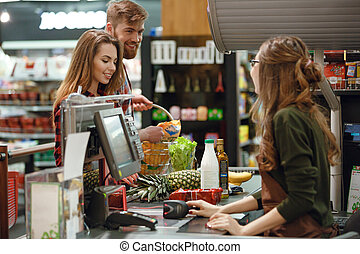 Happy young loving couple standing in supermarket - Image of...