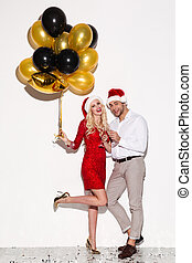 Happy young loving couple wearing christmas hats