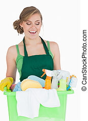 Happy young maid carrying cleaning supplies