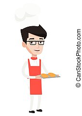 Happy young male baker holding tray of bread.
