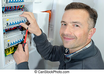 happy young male electrician working on fusebox