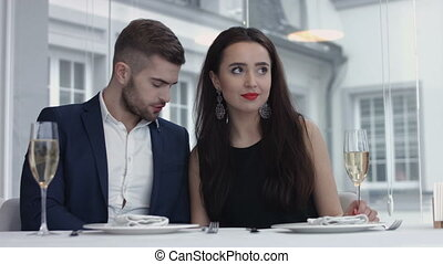 Happy young male proposing with an engagement ring to his surprised girlfriend in a restaurant