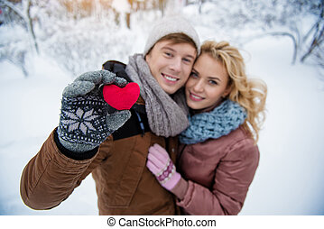 Happy young man and woman embracing in cold weather