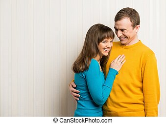 Happy young man and woman in casual wear standing against wall