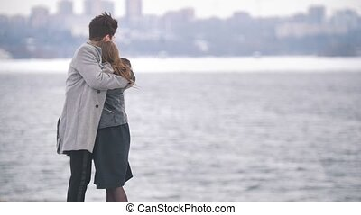 Happy young man and woman kissing on the riverside in cloudy...