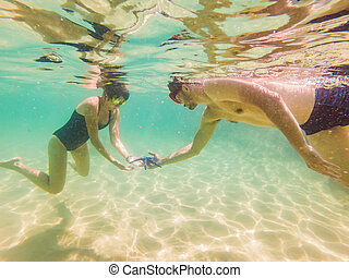 Happy young Man and woman swimming underwater in the tropical ocean