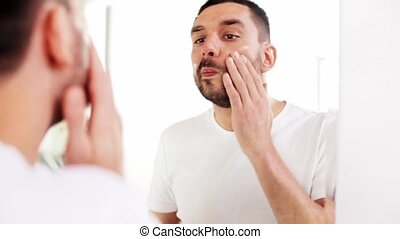 happy young man applying cream to face at bathroom - beauty,...
