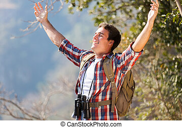 young man arms open on top of the mountain