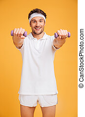 Happy young man athlete standing and working out with dumbbells