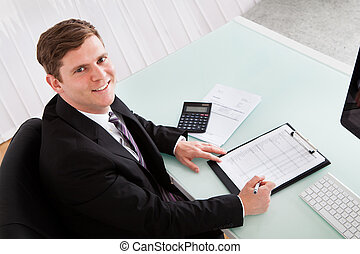 Happy young man calculating finances - Portrait of happy...