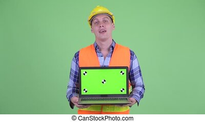 Happy young man construction worker showing laptop and...