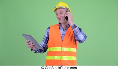 Happy young man construction worker talking on the phone while using digital tablet