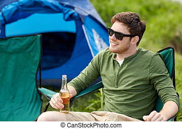 happy young man drinking beer at campsite tent