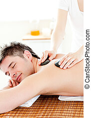 Happy young man enjoying a back massage with hot stone