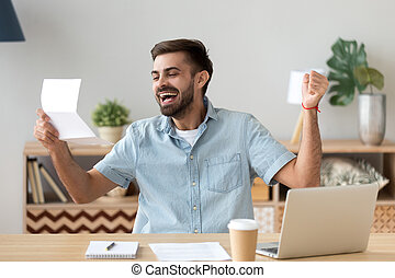 Happy young man excited reading good news holding mail letter