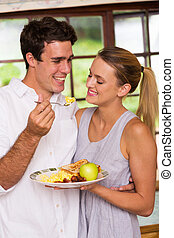 young man feeding his girlfriend breakfast