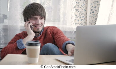 Happy Young Man Freelancer Working with Modern Laptop and Phone in Cafe taking Cup of Coffee