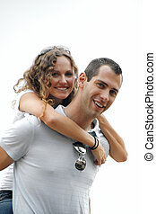 happy young man giving smiling beautiful woman a piggyback ride